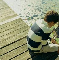 デッキに座って湖を覗く少年 24007000167| 写真素材・ストックフォト・画像・イラスト素材|アマナイメージズ