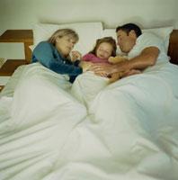 ぬいぐるみを抱いて寝る少女と父と母