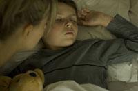 ぬいぐるみを抱っこして眠る少年と母親