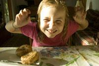 朝食のベーグルを食べる少女 24007000203| 写真素材・ストックフォト・画像・イラスト素材|アマナイメージズ