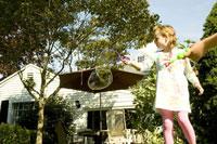 庭でシャボン玉で遊ぶ少女