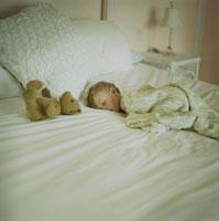 ぬいぐるみと一緒にベッドに寝ている男の子