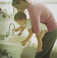 母親に抱っこされながら歯を磨く男の子