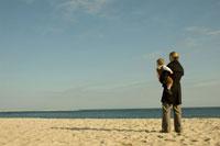 ビーチで男の子を抱っこしている母親