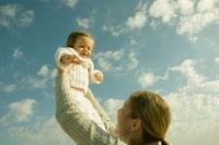 女の子を抱き上げる母親
