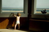 窓辺から外を見ようとしている男の子 24007000366A| 写真素材・ストックフォト・画像・イラスト素材|アマナイメージズ
