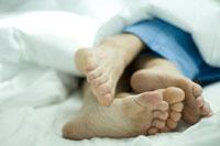 ベッドで寄り添って寝ているカップルの足