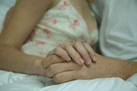 ベッドで寄り添って寝ているカップルの手元
