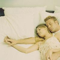 ベッドで寄り添って寝ているカップル