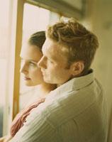 寄り添って窓の外を眺めるカップル
