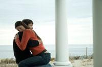 ポーチで抱き合いながら座っているカップル
