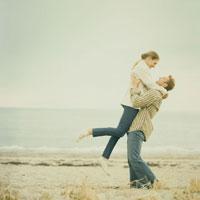 浜辺で抱き合いはしゃぐカップル