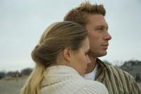 浜辺で寄り添い景色を眺めるカップル
