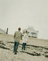 浜辺で手を繋ぎ歩くカップル