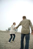 浜辺で手を繋ぎ歩くカップル 24007000442| 写真素材・ストックフォト・画像・イラスト素材|アマナイメージズ
