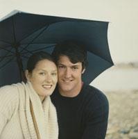 海岸で傘をさすカップル