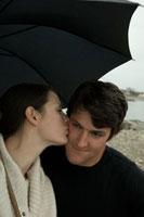 傘の下で男性の頬にキスをする女性