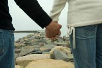 海岸で手を繋いでいるカップルの手元