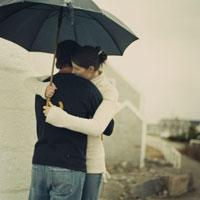 傘をさし抱き合うカップル