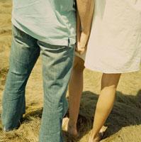 手を繋いで寄り添うカップルの足元