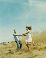 草原の中で手を繋ぎはしゃぐカップル