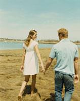 草原の中で手を繋ぎ歩くカップル