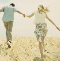 草原の中を走り抜けるカップルの後姿