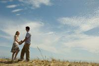 草原の中で手を繋いでいるカップル