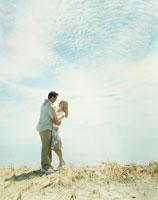 草原の中で寄り添うカップル 24007000490| 写真素材・ストックフォト・画像・イラスト素材|アマナイメージズ