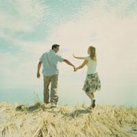 草原の中を歩くカップルの後姿