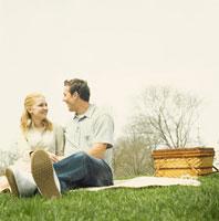 芝生でピクニックをするカップル