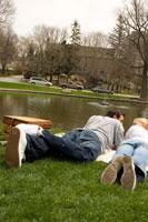 芝生に横になり寄り添うカップル