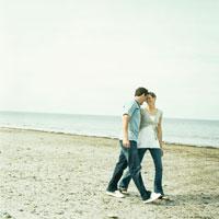浜辺を寄り添って歩くカップル