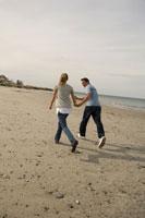 浜辺で手を繋いで走るカップル
