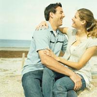 海岸で寄り添い笑いあうカップル