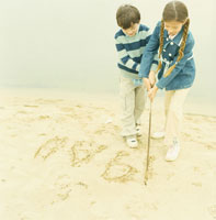 湖の砂に枝で文字を書く男の子と女の子
