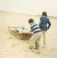 砂浜にある壊れたボートで遊ぶ男の子と女の子