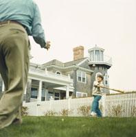 庭の芝生で野球をする孫息子と祖父