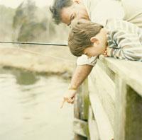 湖で釣りをする祖父と孫息子