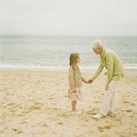 浜辺で手を繋ぐ祖母と孫娘