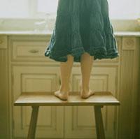 キッチンで台の上に立つ少女の足元