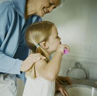 歯を磨く孫娘と、笑顔の祖母