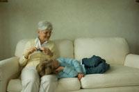編み物をする祖母の膝に寝る孫娘