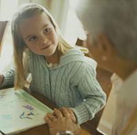 祖母の隣で絵を描く孫娘