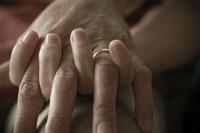 手を握り合うシニアカップルの手元