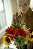 花を活けるシニア女性