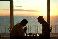 海辺でチェスをするシニア男性2人