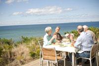 海辺のテラスで食事を楽しむシニアカップル2組