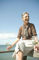 海辺のテラスで談笑するシニア女性