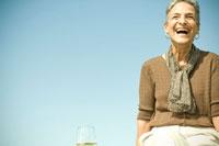 青空をバックに笑うシニア女性